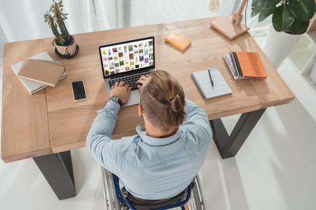 high angle view of disabled man on wheelchair using laptop with pinterest website