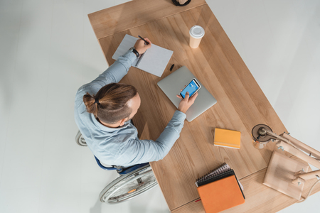 high angle view of disabled man on wheelchair using smartphone at workplace in office