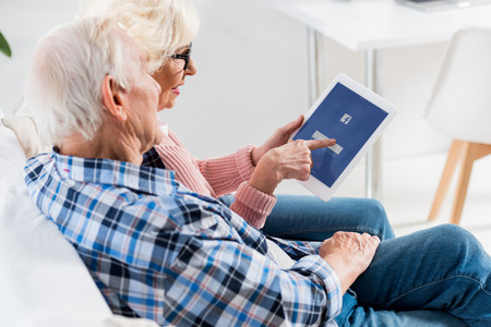side view of senior couple using digital tablet with facebook logo together Редакционное