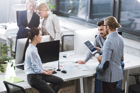 selective focus of businesspeople having discussion at workplace in office