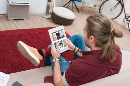 man sitting on sofa while using digital tablet with pinterest appliance Editorial