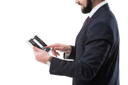 Cropped view of businessman in suit using digital tablet with linkedin website, isolated on white