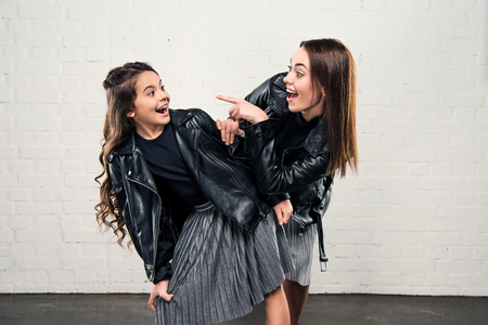 Laughing stylish mother pointing on smiling daughter Stock Photo