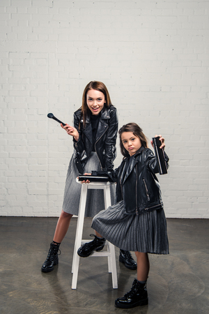 fashionable Mother and daughter with makeup brush and hair spray Stock Photo