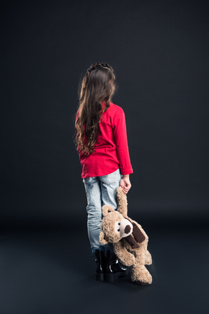 Rear view of kid holding teddy bear isolated on black