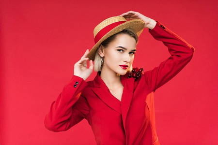 attractive stylish girl in red jacket with boutonniere and straw hat, isolated on red
