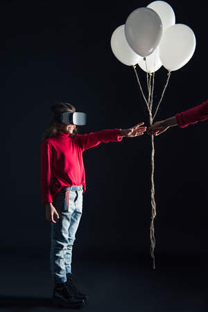 Cropped image of mother giving bundle of balloons to daughter in VR headset isolated on black