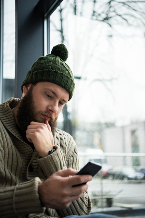pensive man in winter clothes looking at the smartphone