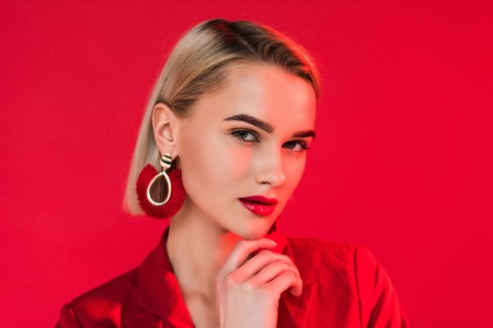 attractive fashionable girl posing in red jacket and earrings, isolated on red 写真素材