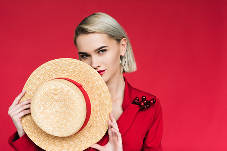 beautiful fashionable girl in red jacket with boutonniere and straw hat, isolated on red Stock Photo