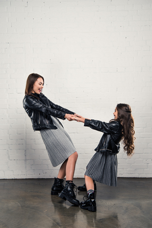fashionable Mother and daughter holding hands and spinning together