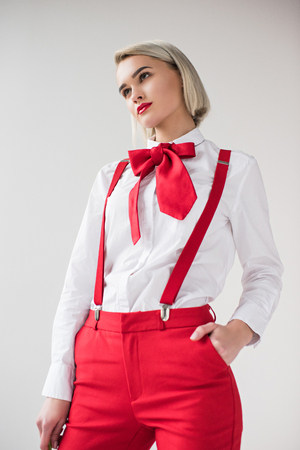 fashionable girl posing in white shirt, red suspenders and bow, isolated on grey