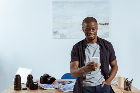 portrait of smiling african american photographer using smartphone while leaning on table with photographing equipment in office Stock Photo
