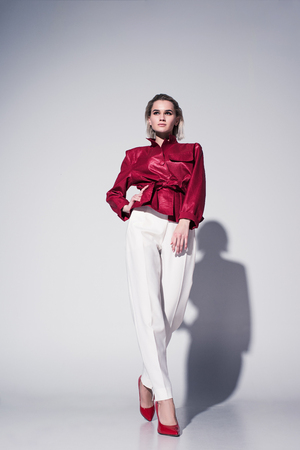 Chica de estilo atractivo posando para sesión de moda, en gris