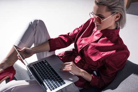 attractive stylish girl in red sunglasses using laptop, on grey Stock Photo