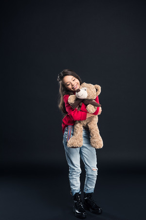 Happy child hugging teddy bear isolated on black