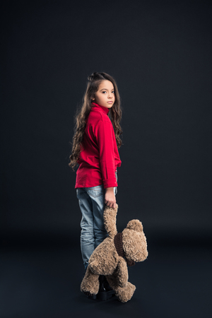 Sad kid holding teddy bear and looking above shoulder isolated on black