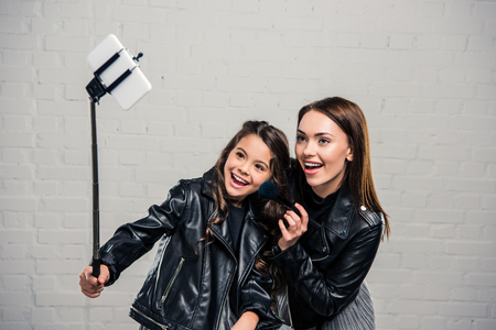 Smiling stylish Daughter and mother taking selfie with selfie stick Stock Photo