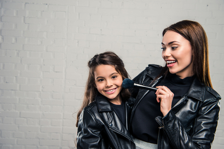 Smiling stylish mother applying pressed powder on daughters face