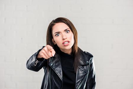 Femme en colère se quereller et pointer sur quelque chose