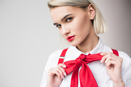 stylish girl posing in white shirt, red suspenders and bow, isolated on grey