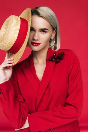 attractive girl in red jacket with boutonniere and straw hat, isolated on red