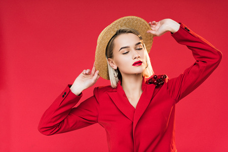 beautiful girl in red jacket with boutonniere and straw hat, isolated on red