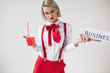 stylish girl posing with red drink and business newspaper, isolated on grey