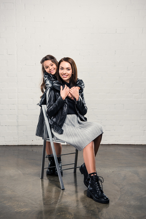 Smiling stylish Daughter hugging mother from the back while she sitting on chair Stock Photo