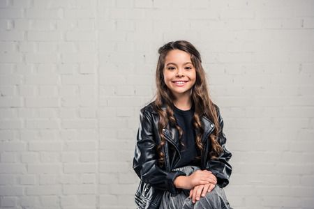 Smiling fashionable kid in in leather jacket sitting on chair and looking at camera