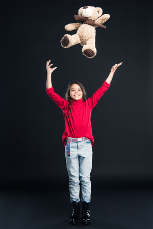 Happy kid throwing up teddy bear isolated on black