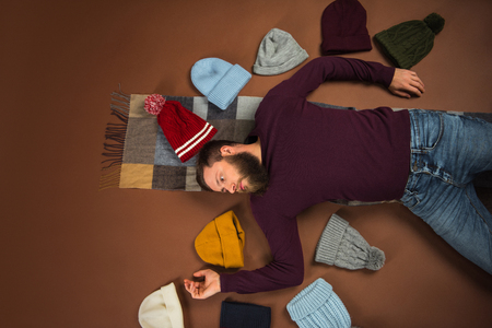 Top view of man lying on floor among hats with open arms isolated on brown