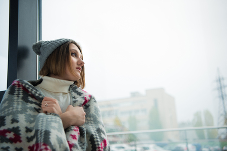Attractive girl wrapped in warm blanket looking at the window Stock Photo