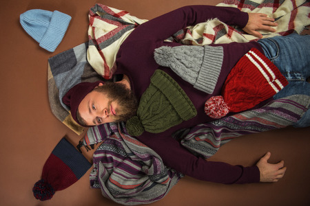overhead view of man lying on blankets between scattered hats isolated on brown