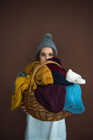 woman showing wicker basket with pile of hats and scarfs isolated on brown