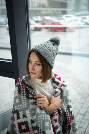 Attractive girl wrapped in warm blanket looking away Stock Photo