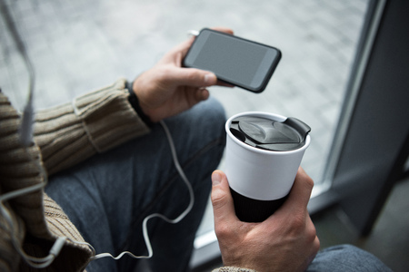Cropped image of man holding thermal cup with coffee and smartphone