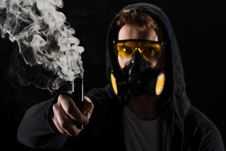 Man wearing protective filter mask activating electronic cigarette Stock Photo