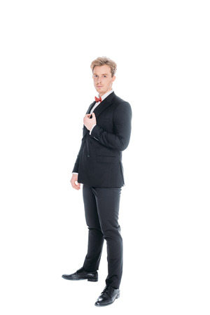 full length view of stylish man in suit and bow tie looking at camera isolated on white