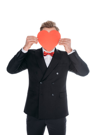 stylish man hiding face behind red heart symbol isolated on white
