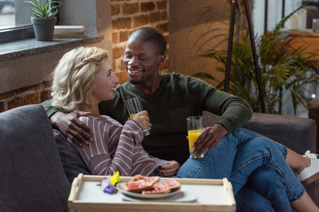 side view of smiling interracial couple with glasses of juice looking at each other at home
