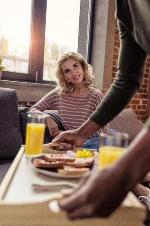 cropped shot of african american boyfriend brought breakfast for caucasian girlfriend