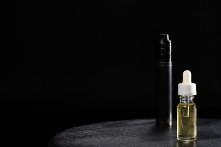 Electronic cigarette and liquid isolated on black