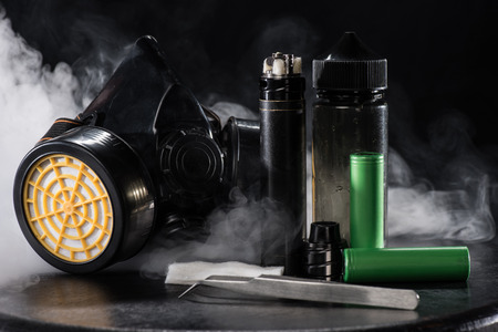 Electronic cigarette and protective filter mask with clouds of smoke on dark background Foto de archivo