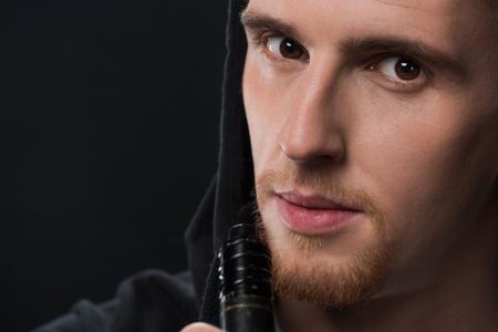 Young bearded man smoking electronic cigarette isolated on black Banco de Imagens