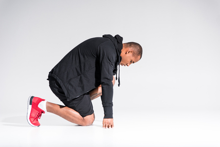 side view of young african american sportsman in hoodie kneeling isolated on grey