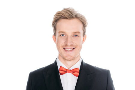 portrait of handsome stylish young man in suit and bow tie smiling at camera isolated on white