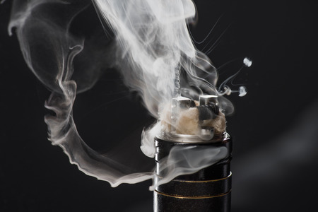 Activating electronic cigarette with clouds of smoke on dark background Stockfoto