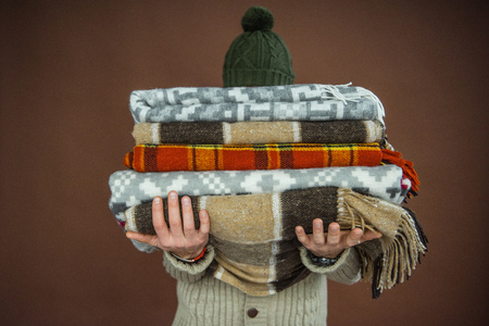man holding pile of blankets in front of his face
