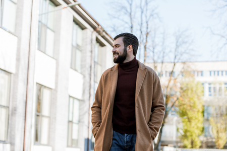 smiling handsome man in autumn outfit looking at side. outside